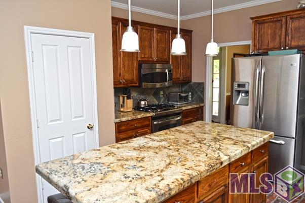 WOOD FLOORS throughout the main living area (foyer, dining, living, halls, and master bedroom) charming red bricks grace the kitchen floors where you'll find a chef's delight: GAS STOVE, STAINLESS appliances, THICK SLAB GRANITE counters, slate back splash, breakfast/keeping area. Formal dining room off to one side of the kitchen and then a large open entrance to the grand living room with a fireplace, view of the courtyard and backyard, off the other side of the kitchen. Laundry room and an EXTRA HALF BATH, conveniently located near the two car carport and back entrance. Master bath has separate shower, vanities, and his and her closets off the master bedroom. There are three more nice sized bedrooms and a double vanity shared full bath. Outside you'll find additional storage and a custom built playhouse in a FULLY FENCED backyard!