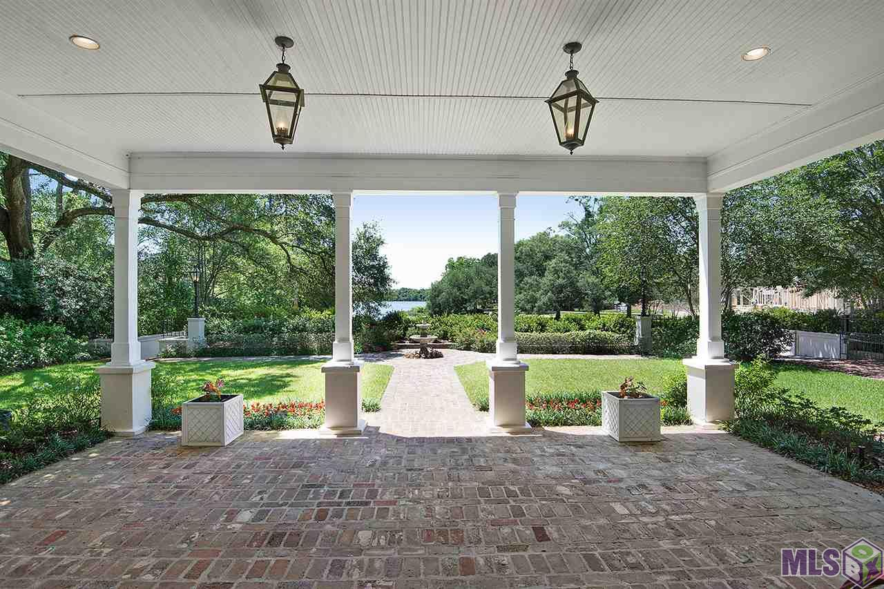 A one-of-a-kind gated property fronting the LSU Lakes with over 5000 sq. ft., a detached suite and an extra lot fronting Hyacinth Dr.! The home features full surround sound and tablet controlled audio in every room, a full home security system which includes inter-com and live cameras, two gated entrances, two porte-cochéres, two guest suites, and elaborate landscaping featuring elegant oaks, lush azaleas and magnolias which creates a park-like backyard. Imagine breathtaking views everyday overlooking the lake with the LSU bell tower and Tiger stadium in the horizon while sitting on over one acre in the heart of South Baton Rouge! Don't miss out on this incredible and once-in-a-lifetime opportunity. Schedule your showing today!