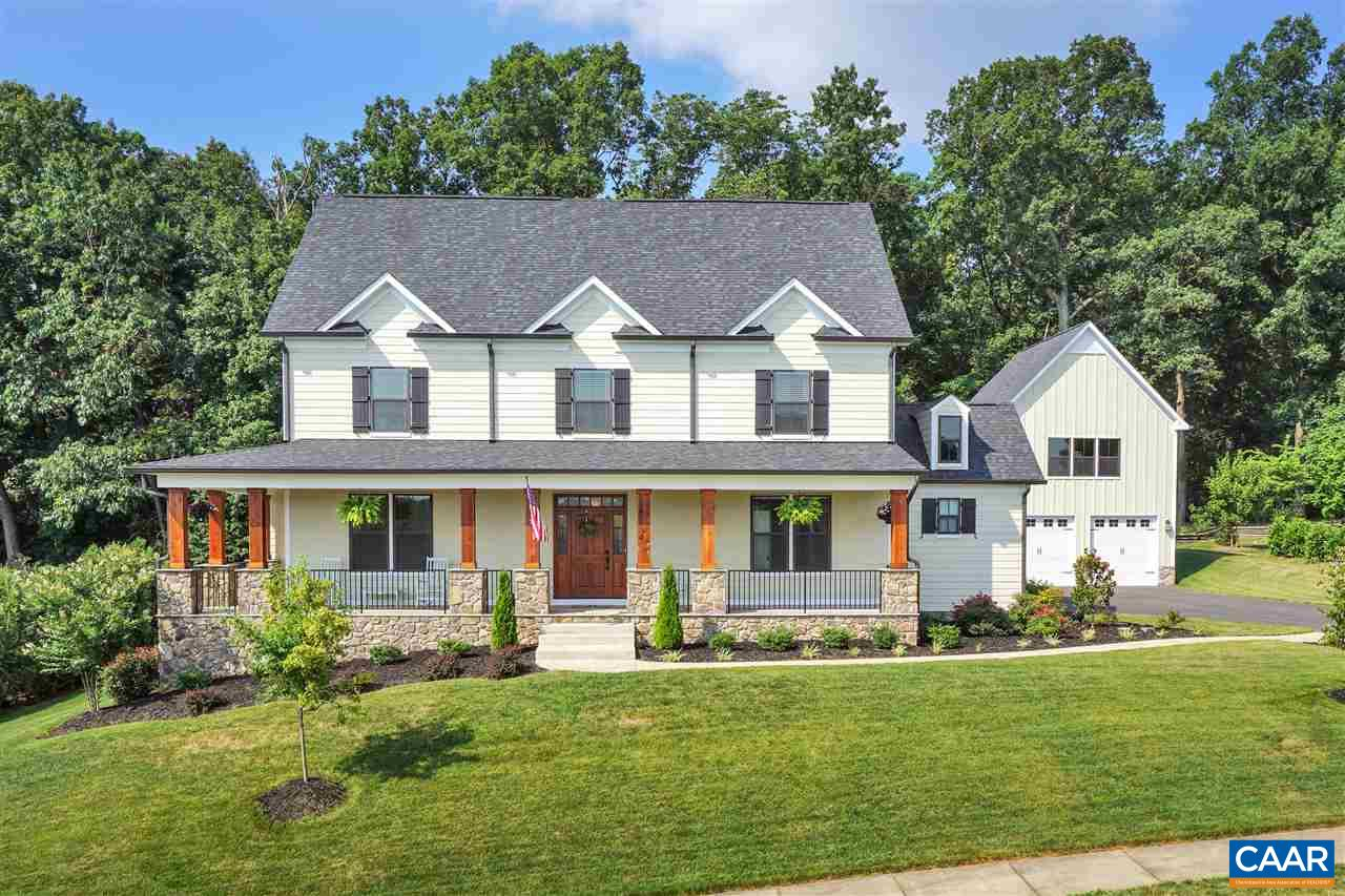 Remarkable 2016 custom built home in Old Trail's Upper Ballard. Backing to woods, the home is well sited to take in huge Blue Ridge views. With a generous open floor plan, 4 en suite bedrooms & 2 half baths, the home lives comfortably & is perfect for family time & entertaining inside and out on the screened porch & patio w/firepit. Cook's kitchen w/commercial gas range, dual dishwashers, farm sink, huge island, pantry, & butler's pantry. Breathtaking master suite and fully tiled bath with dual vanities, double entrance shower & soaking tub. 3 car attached garage and detached 2 car garage w/2nd level finished flex space, wet bar & half bath. Massive storage space. Western Albemarle schools, convenient to all Old Trail and Crozet amenities!