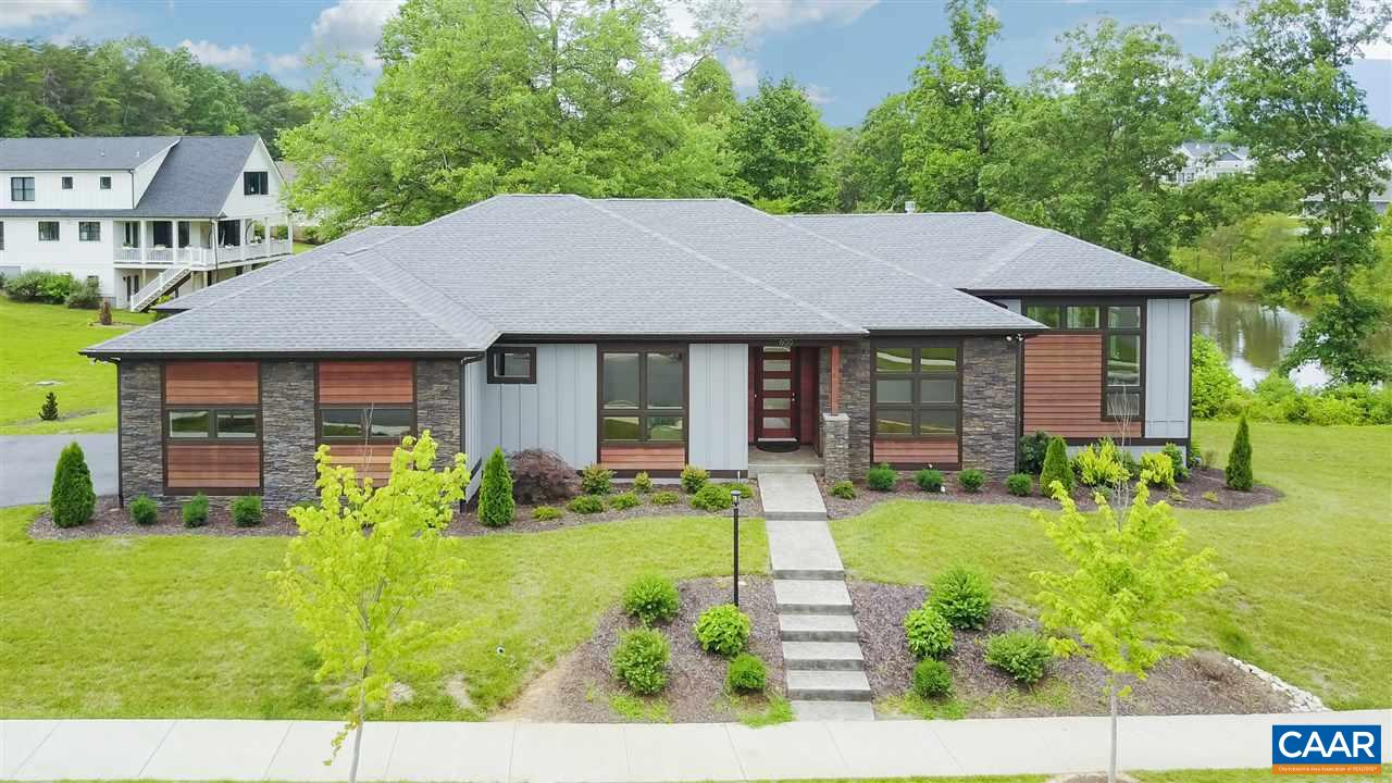 Unique, quality built, custom home with a mid-century modern flair! Like no other home you'll see! Attention to detail through out. Sophisticated finishes in this one-level living home including floor to ceiling Pella windows in soaring great room with 11' ceilings to enjoy the mountain views, quartz counters, custom cabinetry in kitchen and baths and fabulous steam shower. You'll LOVE the sleek chef's kitchen, one of a kind walk through pantry, open floor plan with see-through gas fireplace, huge laundry/mud room with built in cabinetry, finished basement with additional bed and bath, and an over-sized two car garage. Enjoy the spacious screened porch with gas fireplace and outdoor TV overlooking the pond and green space behind.