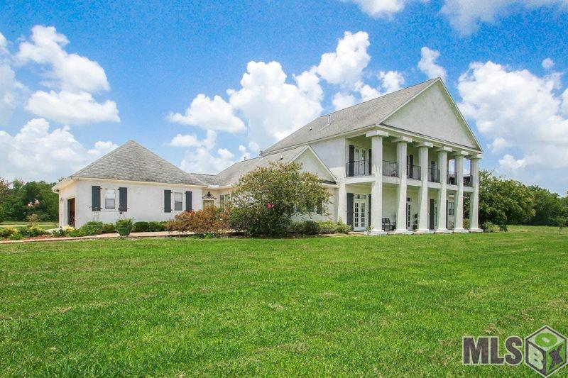 """A beautiful estate on just under 11 acres! A piece of paradise only 10 minutes from the interstate and 15 minutes from downtown Baton Rouge. This Beautiful 6 bedroom or 5BR plus office, 4,048 living sf. home offers picturesque views. Enjoy hunting and fishing? You never have to leave your property to do either! Fish from the stocked pond in your backyard or go deer hunting right from your balcony! Included with the property are two 2400 sf. Work Shop Area/Boat Ports/RV Storage/Barn plus an additional 2400 sf. covered pavilion area. Each workshop has an apartment inside that can serve as income property if rented (one is currently being rented for $1000/monthly)! This 2 story home has 2BR downstairs and 4BR upstairs with 10-foot ceilings and 12"""" crown molding. The living room has a corner fireplace and the gourmet kitchen host granite countertops, 6x5 island, double oven and cabinets galore. Right off the kitchen are a large walk-in pantry and wine room! The open floor plan includes breakfast or sitting area, living, dining and grand foyer with 20ft soaring ceilings. The spectacular wood staircase leads you to loft area plus 4BR and a 40X9 ft. balcony. Home features lovely wood floors throughout w/ tile in bathrooms and a Mom's dream utility room. The property also includes kids playground area and all the privacy you want. All of this plus more sits on 11 Beautiful Acres!!! A Must See!! Call for your private tour!!"""