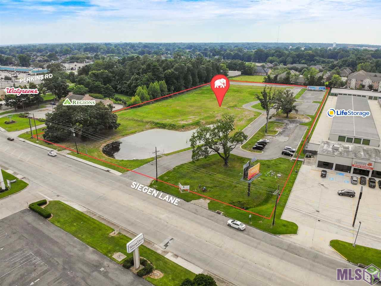 As one of the few remaining development tracts along Siegen Lane north of Perkins Road, this ±7.196 acre parcel presents an incredible opportunity for a new high-profile development. The lot not only features ±388 feet of frontage along Siegen Lane, it is already poised for development with infrastructure improvements in place.  Existing infrastructure includes an entrance drive, multiple parking lots, a drop-off drive adjacent to building pad, a retention pond, sewer treatment plant, and foundation piles within the building pad.  The property is zoned for Small Planned Unit Development (SPUD), which allows for a mix of land uses relating to the development of large tracts of land. Many development concepts are possible as permissible uses for SPUD zoning include most commercial uses ranging from A1 (Single-Family Residential) to M1 (Light Industrial).  The property is seen by ±23,600 vehicles per day and would offer excellent visibility to all passing traffic. This section of Siegen Lane is populated with retail, multifamily, and hospitality properties and is surrounded by multiple residential neighborhoods.  Interstate 10 and the large retail development Siegen Lane Marketplace sit just 1 mile north of the property. Perkins Road to the south offers easy access to Bluebonnet Blvd and Pecue Lane.  - Extensive site work and infrastructure already in place (fill, retention pond, drives, parking, sewer, foundation piles, etc.) - Excellent visibility and one of the last large development tracts remaining in area - Ideal for medical, senior living, school, professional office, or multifamily