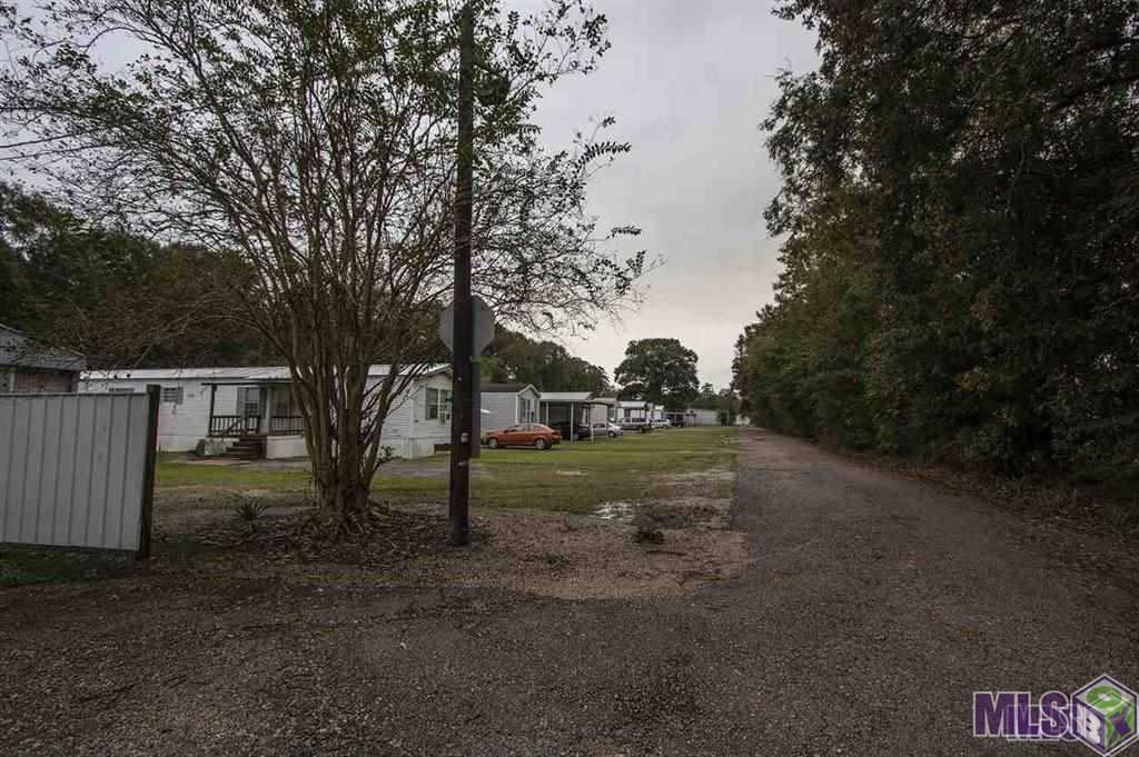 Landry's Mobile Home Park is off of Florida Blvd near Juban Road and Juban Crossing with quick access to I-12. Did Not Flood! Property consists of 13 manufactured homes that stay rented and when there is a vacancy the property immediately leases. All the properties have been well maintained and managed by the owners. There are 2 additional metal building/homes at the rear of the driveway that have living areas and warehouse or shop space. The main house is 2100 sq ft, sits on over an acre with a stocked pond, 2 bedrooms, 2.5 baths, office, garage, a beautiful kitchen with plenty of cabinets, granite counter tops, stainless appliances, ship-lap walls and cathedral ceilings, and large walk in closets. Main house has a 60x20 porch and entertainment area, 40x12 wood deck overlooking pond, a detached 39x45 workshop of which 30x45 completely insulated with front and back roll up doors, a 34x24 equipment shed and separate 21x19 tractor shed and a lot of concrete parking area. 2nd metal home is currently rented 4800 under roof with 2200 living and a decked second flood, 2600 shop area and 3 car carport. Financials are provided upon qualified buyers request.
