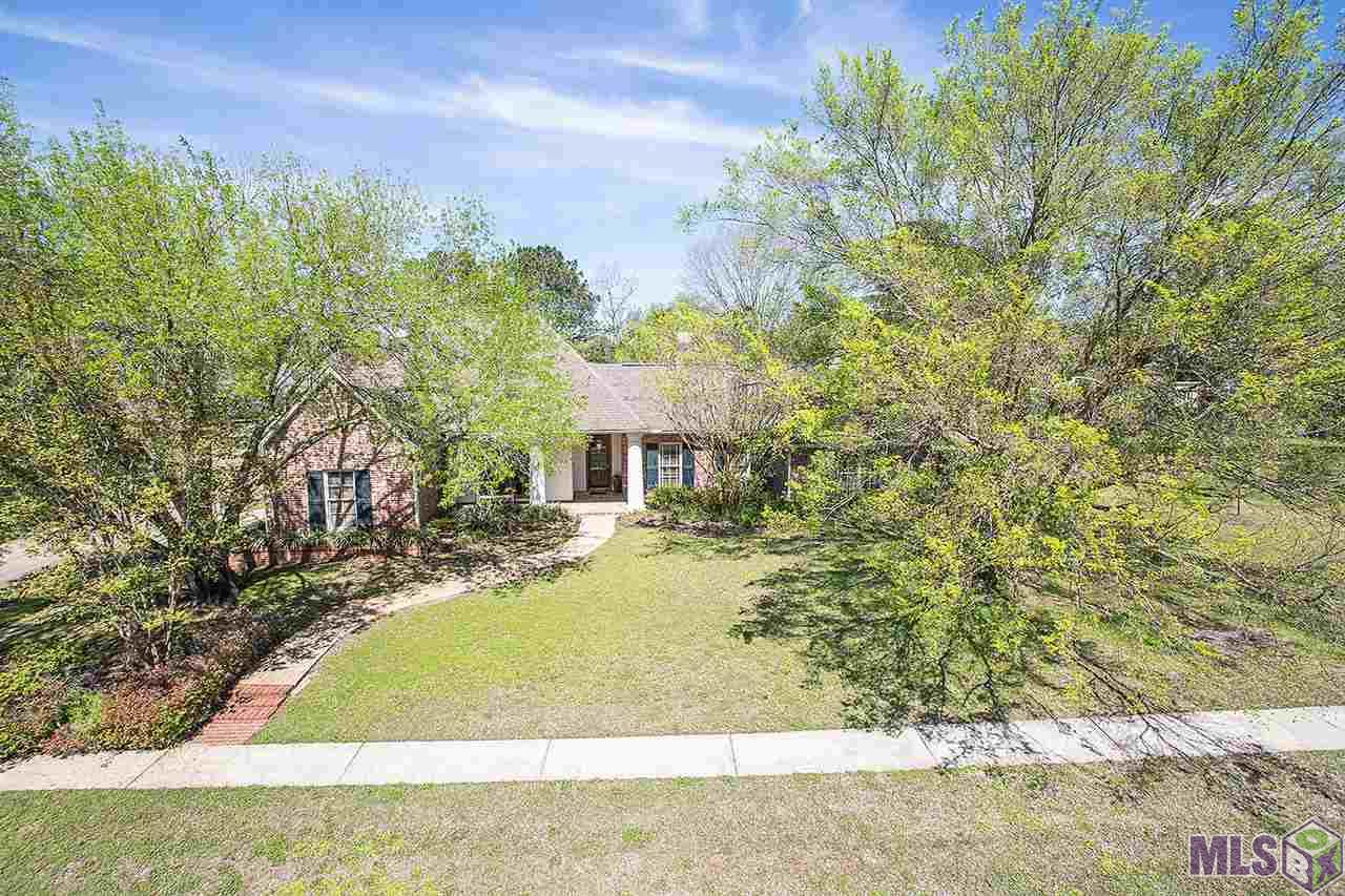 """YOU WILL LOVE this beautiful custon built, wonderfully landscaped, home on huge corner lot (double lot), in one of the most desirable neighborhoods in the heart of Zachary-#1 school district in the State of Louisiana! The outside highlights of this home are the large, private, corner lot, 3-car garage, beautiful gunite pool with hot tub, fountain and tropical landscaping, large porch areas in front and back yard, all guttered, beautifully landscaped. Also high and dry; the drainage around house was professionally done, with 6"""" french drain under ground, and meshing under grass keeps water AWAY from the house, and yard doesn't hold water. The custom details continue inside this home with a great floor plan, large bedrooms, and large closets, lots of cabinets/storage, and large living areas. The character of the full brick, and old pine flooring catches your attention the moment you walk in the door. These floors were salvaged from an old Coca-Cola building and give this home something special. The custom details are apparent throughout this entire home, inside and out. This is truly a gem in the heart of Zachary. Walking distance to Zachary High School."""