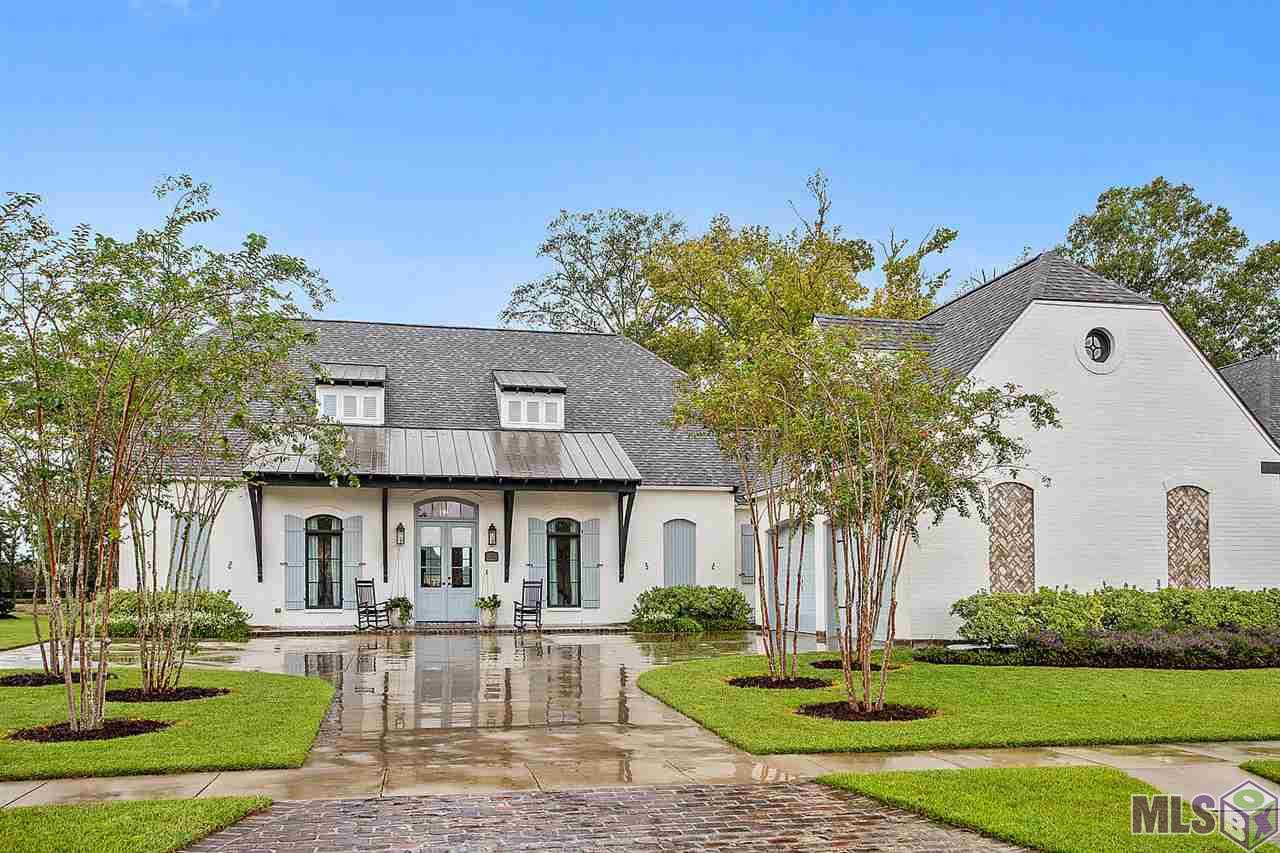 STUNNING CUSTOM HOME in Clairmont Subdivision! Welcome to this friendly neighborhood with waterfront views and walkways located in the Zachary Community School District. This 4BR/4BA home has 3,088 sqft of living space with office and double garage. Once a contractor's personal home, no details have been spared. The dream kitchen boasts a repurposed one-of-a-kind island, custom wooden oven hood with intricate trimming, floating shelves, subway tile backsplash, oversized farmhouse sink, marble counters, commercial appliances, gorgeous wide plank reclaimed wood floors, and reclaimed wood ceilings. Open kitchen/living/dining area is perfect for indoor entertaining, including reclaimed beams and rare, oversized fireplace mantle with imported corbels. Not to be missed are the imported doors and high ceilings throughout. Spacious master suite includes another gorgeous fireplace, ensuite master bath with custom shower, soaking tub, stained glass window, double vanities, and walk-in closet. Two bedrooms rooms off foyer, each with adjoining bathrooms. Bonus bedroom upstairs with private bath. The outdoors are just as impressive with back porch entertaining space and egg for cooking, lush landscaping, and private garden. Don't miss this custom designed masterpiece! Schedule your showing today!