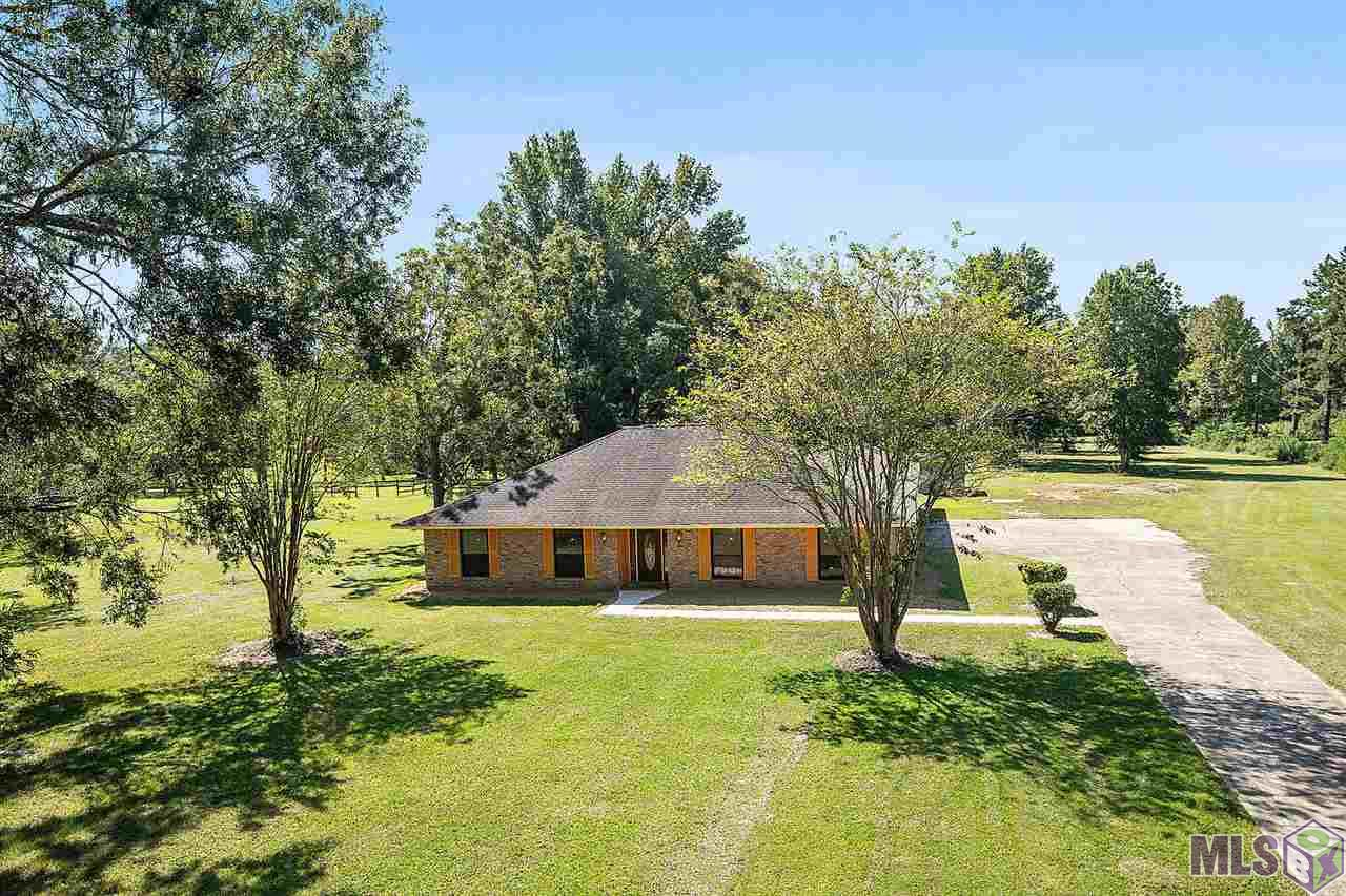 Located off of Old Scenic Hwy. country living with all the amenities that Zachary has to offer. This beautiful home is located on the front part of its massive 4.5 acre lot and greets you with a spacious front yard with beautiful trees all around. When you walk into the home you will notice the open floor plan. This area is perfect for the gathering of friends and family. The living area has beautiful wood floors that flawlessly transition into tile in the kitchen. The kitchen off to the left offers a large granite counter top island with available bar seating. The breakfast room seamlessly fits into the large open floor plan that adds plenty of seating. The 3 bedrooms and 2 bathrooms are on the opposite side of the house. The spacious master en suite bedroom offers multiple closets with one being a walk-in. The bath has a jetted tub/shower combo with a separate water closet. With it being on a 4.5 acre lot, the backyard seems endless with a country living feel. The back yard has a spacious storage/workshop that has a wall AC unit.
