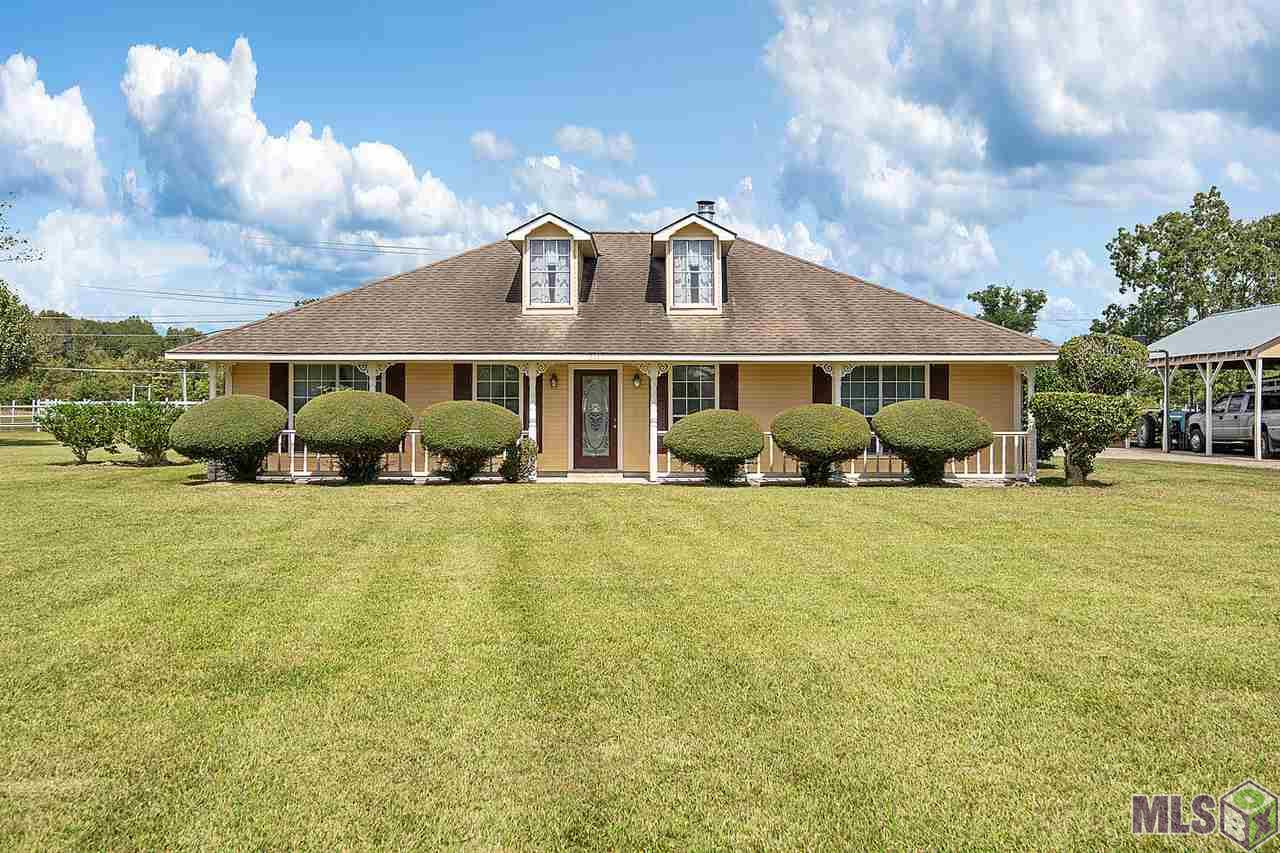 Stunning, well maintained home on 4.08 acres in Zachary!  This amazing property features tons of amenities and has so much to offer both inside and out all located in the #1 school district in the entire state of Louisiana!  Explore this spacious 3 bedroom 2.5 bathroom home with beautiful laminate wood flooring in the oversized 20 x 21 living room with cozy corner wood burning fireplace and tray ceilings, updated paint throughout the entire home, spacious master bedroom with en suite master bath, 2 additional generous sized bedrooms, full bath, and kitchen with breakfast nook perfect for family meals! In addition to the beautiful curb appeal & landscaping, enjoy time on the relaxing front porch area and take in the essence of the large acreage lots in this neighborhood!  The outdoor amenities includes an oversized 22 x 22 garage, additional boat garage with half bath, more covered parking large enough for a RV or farm equipment, huge 40 x 50 barn with 4 horse stalls, hay storage area, additional storage space, sliding doors at front and rear with a private Man Cave and Tact Room sealed with insulation! Pasture is fenced and crossed fenced for rotating and grazing, front pasture is fiberglass pipe, and rear is net wire with 50' round pen for horse training!  You do not want to miss out on this amazing property, schedule your showing before it's too late!!!
