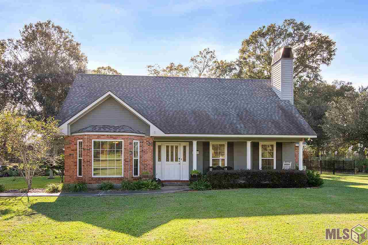 Live in The Plains! This two-story, 3 large bedroom/2.1 bath home is on a beautiful 1.67 acre lot with large trees in the Zachary School District! This well-maintained home did not flood and was updated in 2015. The open floor plan boasts a fireplace, granite, quartz, porcelain and solid wood floors with no carpet anywhere in sight!  You will love the under-cabinet lighting and dimmers to go along with the built-ins and pull-out shelving, the master has a gorgeous bay window and the bath even has a hidden storage area! Both bedrooms upstairs offer cathedral ceilings and  the bathroom is full of storage! The beautifully-landscaped yard is partially fenced with wrought aluminum and there's plenty of room to park with a cool basketball area!  Come sit under the covered patio and listen to all the birds!