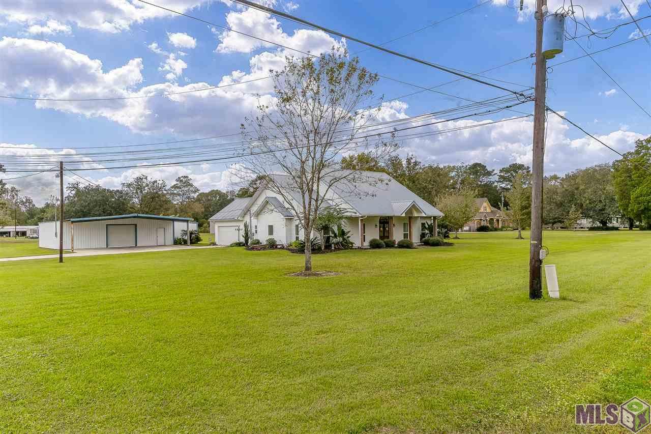 This beautiful home sitting on 1.67 acres in Ascension will definitely catch your eye with its beautiful wood columns and front door and massive shop! This 3 bedroom, 2.5 bathroom house with almost 2200 living sq. ft. is perfect for you growing family! Need a 4th bedroom? No problem! The 256 sq. ft. detached building would make a perfect additional bedroom, office, air-conditioned storage, she-shed, or whatever you please. If that doesn't work for you, there are stairs already built when you open a door leading up to the attic. The space is all open to build your 4th bedroom, game room, workout room, or whatever you please. All you outdoorsman, you will love the 40x40 workshop with an oversized roll up door for all your outdoor vehicles, outdoor or sports equipment, workout equipment, and more. The kitchen is farmhouse perfection with the custom pantry door, granite countertops, gas stove, farmhouse sink, white cabinets and stainless steel appliances. Recessed lighting throughout the extremely spacious dining area and living room create bright open rooms for entertaining. The high ceilings, two large industrial sized fans, wood floors, built in shelves and fireplace make the living area a true beauty. Master bathroom features high ceilings, double vanity, soaking tub and separate shower. All appliances will remain including the fridge, washer and dryer! AC was replaced in 2017. Contact us for more information or to schedule a private showing!