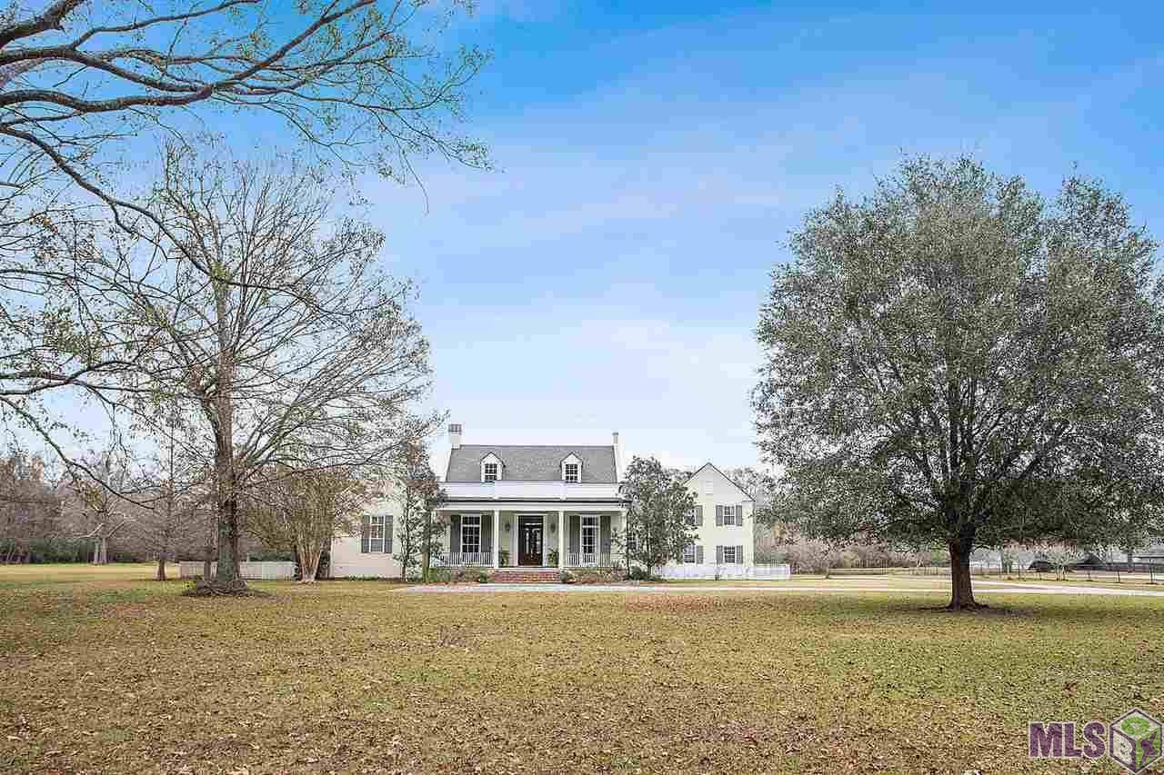 A perfect display of southern charm is offered by this beautiful custom designed home and the 3.37 acres that it sits on.  Think country feel without having to drive all the way out to the country.  Upon arrival you are welcomed by a large front yard and a most inviting front porch.  Enjoy access to the pond in the back along with more wide open space that the back yard gives.  A comfortable screened in back porch and an upstairs balcony offers views of it all.  The formal dining, formal living, foyer and den all feature heart of pine floors.  A spacious kitchen opens to the breakfast area which rests under a vaulted wood stained bead board ceiling. In addition to the four bedrooms, the home also has an office with custom built-ins.  There are two separate upstairs areas.  One has two bedrooms and a Jack & Jill bath.  The other has a large bedroom that could also function as a bonus room.  The home's roof was replaced last year, as was the dishwasher.  Other amenities featured are a sprinkler system in the flower beds, surround sound in den, master and back porch, three HVAC systems and two water heaters.