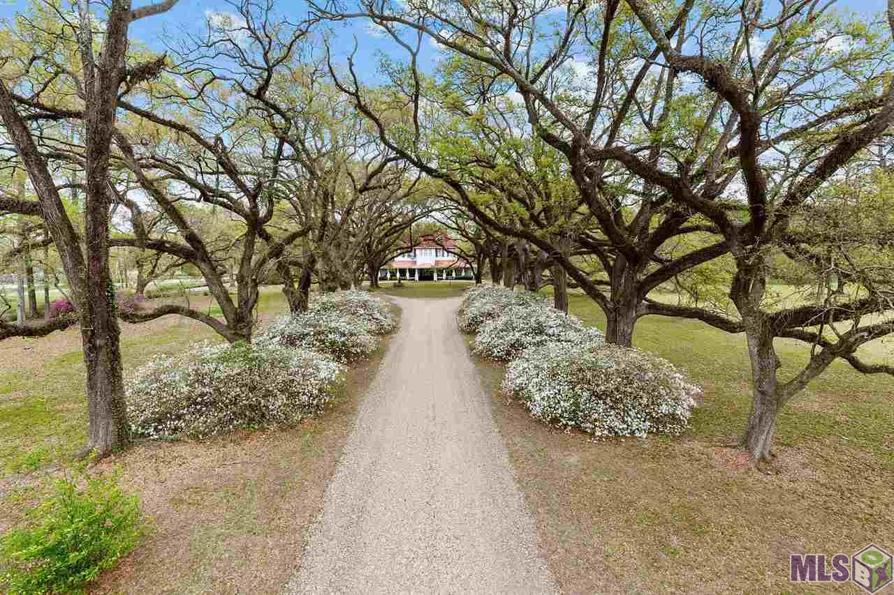 Yes!! It's THAT house!!!  Step back in time in this turn of the century home nestled beyond a canopy of mighty Live Oaks. Historic Shadowfield of the Plains was built in 1913. This timeless beauty is a one of a kind, featuring sprawling landscaping, an outdoor get a way spot with FP, 3 ponds, a caretakers cottage, 20 x 40 barn on this 25 acre estate. The home is a virtual treasure trove of another time. Enter thru the Port Cache and welcoming wide veranda wrap porch to the grand foyer (FP) with double open staircase leading to open landing sitting area with huge bedrooms, and sun room.  Ballroom size living room with 9' walk thru windows to porch, 12' ceilings (Now being used as a Business, craft, floral room). Master bedroom (FP), Dressing room, bath & study (FP).  Continuing on to the open sitting area - is informal dining area and office with beautiful views of the landscaped grounds. Fabulous formal dining room with Beautiful coiferred wood ceiling. Kitchen and breakfast area overlook grounds and pond.  4 working fireplaces inside, 1 outside. 100 year old wood flooring. Too many unique amenities to name. This wonderful home does need some TLC, price reflects. This Gem on such beautiful property would be the perfect home; fabulous Bed & Breakfast, Amazing Venu for Weddings and Events; or Romantic Restaurant. Come take Your Private Tour!
