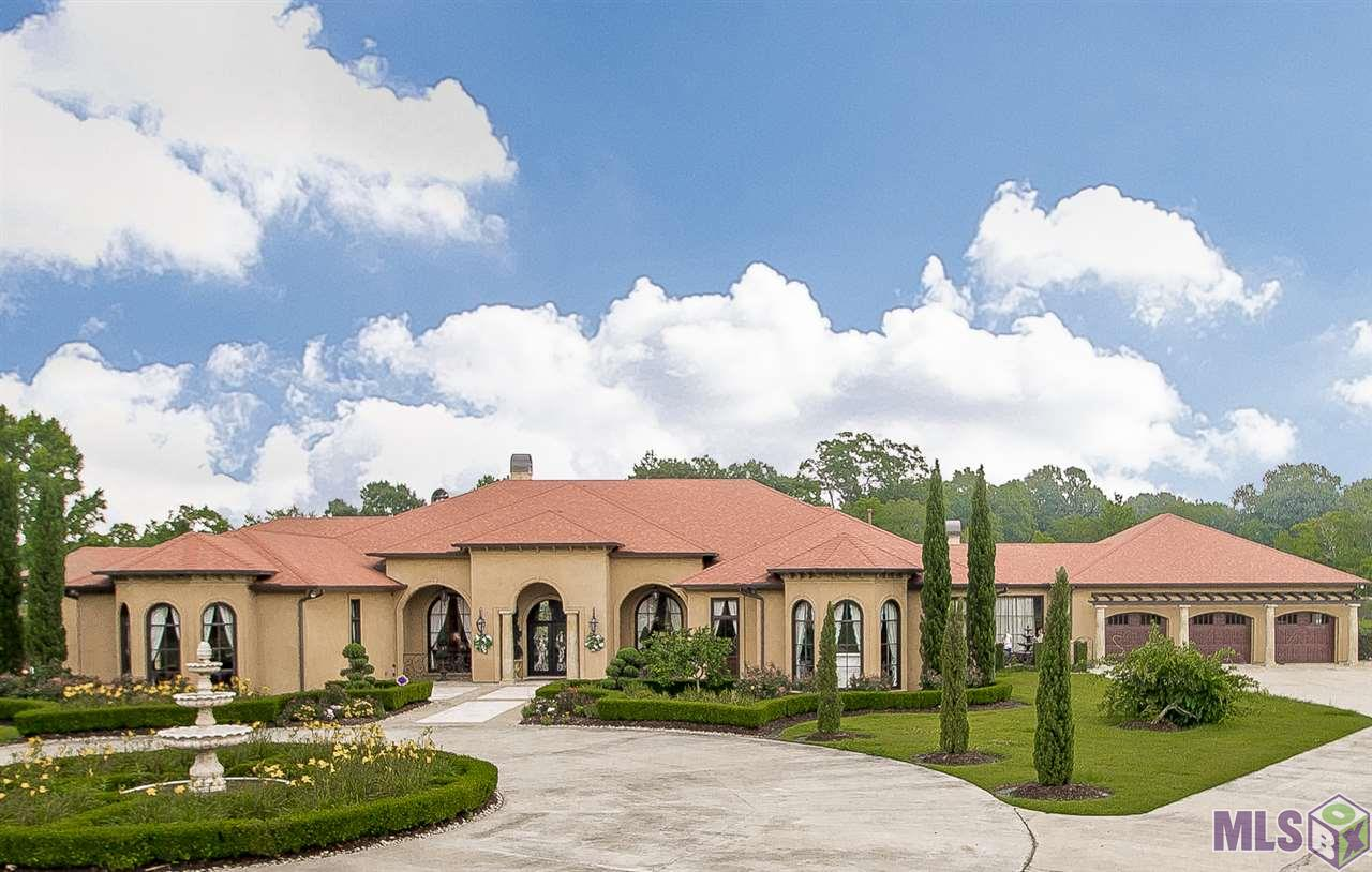 One of a kind private & luxurious Mediterranean Estate tucked away on 6.27 acres. Entire property is beautifully landscaped & fully fenced with gated entrance. Built in 2011, this exquisite custom home exhibits unsurpassed style, quality & sophistication including beautiful archways, columns, beams, oversized arched windows with gorgeous views, coffered ceilings & travertine floors inside & out. Main house boasts 6,316 living area, soaring ceilings, 4 large bedrooms, 3 full & 2 half baths, billiard room, movie theater, wine room, executive office & super abundant storage. Living & dining rooms with arched rear windows are beautiful & inviting.  Master bedroom offers a welcoming sitting area with wood burning fireplace overlooking the beautiful outdoor oasis. Unbelievable master bath BEYOND LUXURIOUS with Van Gogh quartzite countertops & around tub, new hardware on faux painted cabinets, barrel ceiling, enormous walk-in shower with new tile flooring & walls accented with mirror tiles leads to private outdoor courtyard, his/her vanity areas & oversized his/her closets. Open kitchen has been completed updated with gold cristallo quartzite, mirror tile backsplash, new hardware & abundance of cabinets faux painted in pale blue, stainless steel SubZero & Wolfe appliances & large substantial island with breakfast bar. Keeping room with fireplace, breakfast area & wet bar opens to an extra large covered porch with fireplace, multiple sitting areas and gourmet outdoor kitchen/keeping area with island. Enjoy this resort style outdoor haven including magnificent pool & spa area, vegetable garden, volleyball court & 2 fully stocked fishing ponds. Adjacent to pool area is adorable 2 bedroom guest house complete with full bath & kitchen. Master suite, office, living, dining, kitchen & keeping area all enjoy views of outdoor living area. Additionally, the property boasts boat storage, cedar closet, 4 wood burning/gas fireplaces, security cameras, full house generator, 3 car garage