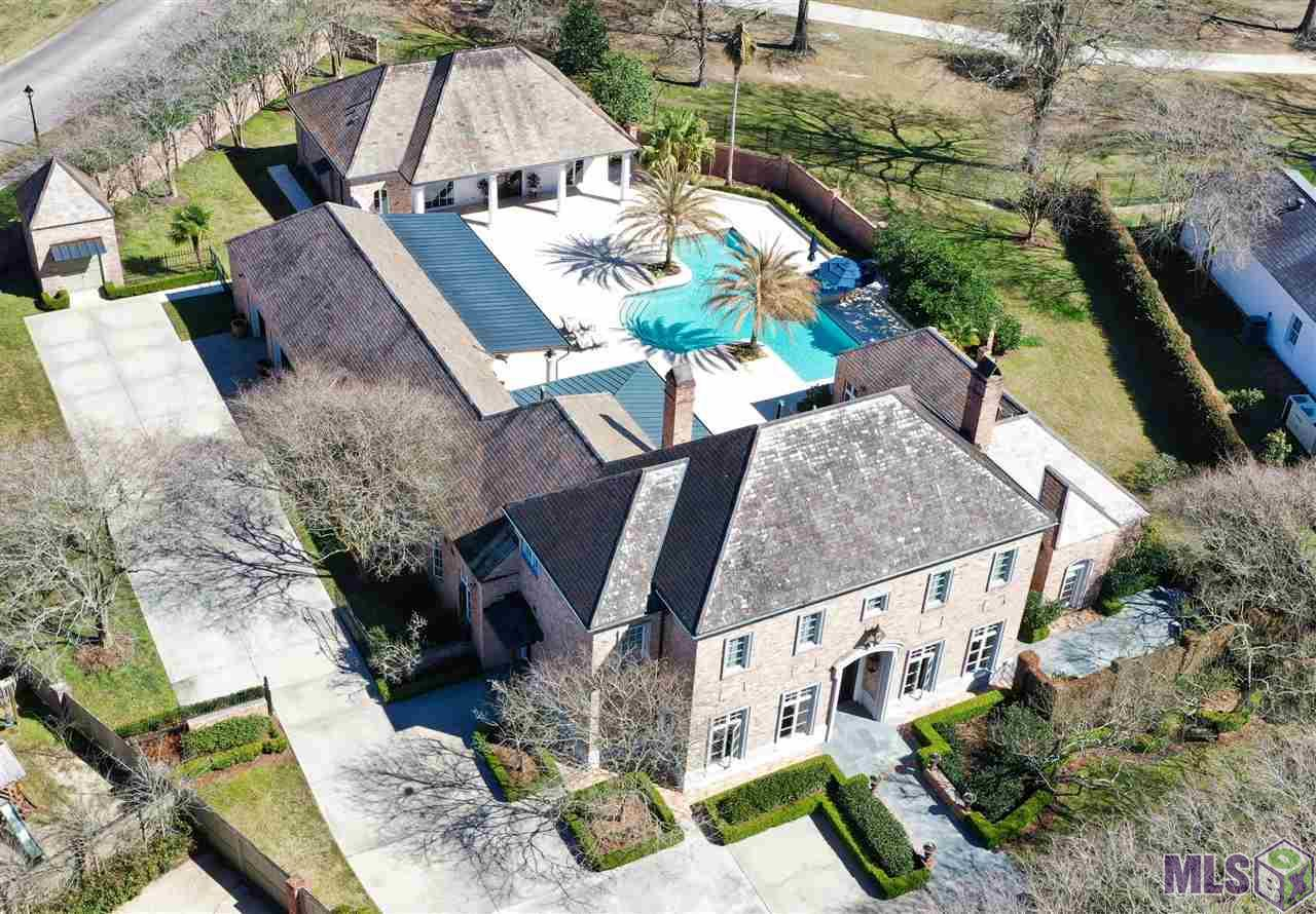 """Located in the heart of one of Baton Rouge's most sought after gated communities, this incredible Estate encapsulates timeless beauty, one of a kind craftsmanship as well as being built with integrity to last a lifetime. No words truly depict the reality of this majestic masterpiece, A MUST SEE TO BELIEVE. Built on over an acre, overlooking Hole #5 of the prestigious CCLA golf course, this one-of-a-kind Jewel leaves nothing to be desired. Jam packed full of priceless features and versatility with 5 bedrooms, 4 and a half baths, 3 laundry rooms, massive bonus room/theatre/home office with all technological abilities imaginable, the master suite on its own wing with private courtyard, cedar plank walled Pigionaire wine cellar, full workshop and the list goes on. Leaving nothing to be desired, the chef's kitchen is dressed in professional series Viking appliances, brand-new Sub-Zero refrigerator/freezer, beautiful brick floors, cedar plank ceiling, granite counter tops, large island and plenty of storage. Giving the feeling of living your best life or channeling your inner Jimmy Buffet, step out the back door and get swept away by the serene resort like amenities which make every day at home, feel like a vacation. This estate is the true definition of having your cake and eating it too. No expense was spared with this home, plus the newly rebuilt 4,000 square foot sanctuary which includes a New gunite pool and spa with Nature 2 mineral saltwater system, gourmet outdoor kitchen finished with Twin Eagles appliances plus granite counter tops, 2"""" thick custom cut Ivory travertine stack stone decking, commercial grade drainage, double brick fencing and much more. Finally, the separate 1,550 square foot guest house with open floor plan, full catering kitchen equipped with Viking appliances, massive living room adorned with custom built ins and space galore. Ready to make your Dreams a Reality…. come see for yourself!"""