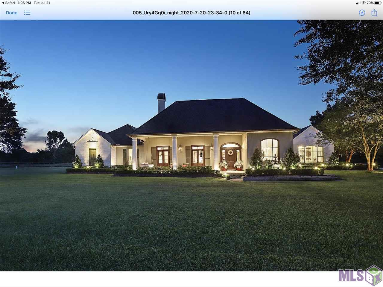 ABSOLUTELY STUNNING is this one-of-a-kind Luxury Home in a highly desirable area of Zachary.  Situated on over 14 acres, this enclave allows you to experience the privacy and freedom of country living while being only a few minutes from the center of town.  As you enter the gated property, you'll see the sprawling, stocked pond hosting seasonal guests like ducks and geese.  The home is tucked within several live oak trees and extensive landscaping, while donning limewashed brick, showcasing it's traditional architecture.  The house is almost 4000 square feet and has been updated with modern aesthetics while preserving its craftsmanship and style.  Featuring 4 bedrooms, 3.5 bathrooms and an office/Bonus/Recreational room, large kitchen with a sitting area and custom bar, spacious dining room and natural light filled, expansive Living/Family room overlooking the pool and patio.  The main suite also overlooks the pool and includes a segmented sitting room/office area and a newly renovated luxury bathroom and master closet with custom built-ins.  Each additional bedroom accesses an ensuite bathroom and includes walk-in closets with custom built-ins. The pool area features a spacious patio, waterfall, iron safety gate and lanai enclosure, allowing for bug and debris free enjoyment any time of the year.  Listen to music indoors or outside while lounging in the saltwater pool with the integrated home surround sound system.  Enjoy the backyard views of the barn that includes an Apartment/Guest home, 2 storage bays and large covered porch with a swing.  Further back on the property, the Barn includes 3 stall stables situated with a large paddock, and includes a washing station and tack room.  All of these structures are supported by a whole-property generator to ensure that you, your guests or your animals are never without power.  THIS ONE IS A MUST SEE.