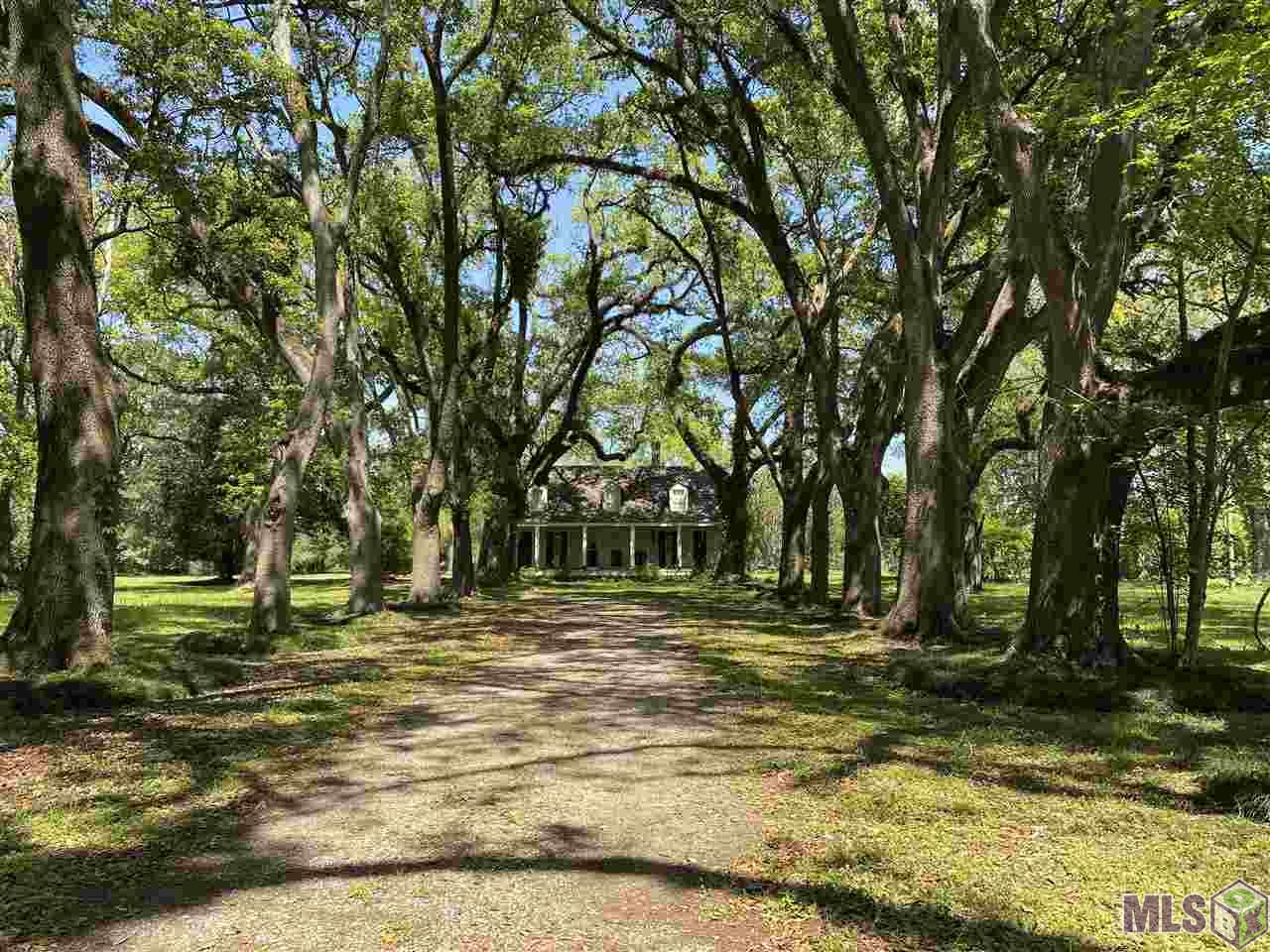 """Own a piece of Baton Rouge history on Highland Road just south of LSU! Previously known as """"The Oaks,"""" this 6.18 acre property presents the right buyer with a rare opportunity to acquire acreage with Centennial Oaks along the historic Highland Road corridor, not far from the south gates of LSU.  Gorgeous live oaks shade the driveway leading up to the home which has been owned by the Duplantier family since the early 1800's. The live oaks provide a beautiful frame for the 4,034 square foot, two-story home, built more than 170 years ago. The elevated front porch has operating shutters separated by three tall windows in the center. Six square columns stand sentinel below three dormers on the roof. Formal dining room. The home's original woodburning fireplace is below the original brick chimney in the downstairs living room, while the large kitchen had been updated several years ago with a Chambers electric cooktop and double wall ovens. The kitchen also has an abundance of cabinetry, dishwasher and double sink below large windows that view the side yard. The master suite has a walk-in closet and sitting area, while an additional two bedrooms with ceiling fans and a hall bath are located upstairs. The home also has a double garage and an inside laundry room. This is truly a rare opportunity to obtain one of Baton Rouge's most familiar landmarks on Highland Road. The bonus is six-plus acres along one of the most desirable residential locations in the city. Call today if you'd like to see this amazing, historical Highland Road property!"""