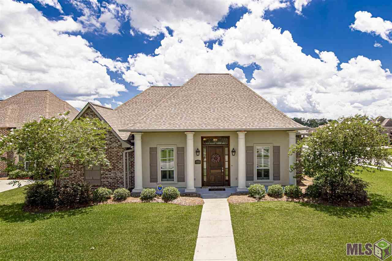 Simply Stunning! This gorgeous 4 Bedroom 3 Bath Acadian Style home sits on a large corner lot in the highly desirable Parker Place Estates Subdivision. Fantastic location!! Just minutes from the newly anticipated Prairieville High School and easy access to shopping, entertainment, healthcare, and restaurants. This home has tons of extras, including a whole home generator, gutters, plantation shutters, and a complete camera security system. The living room features 12ft ceilings with beautiful dirty top pine wood floors, a gas fireplace with a brick hearth, triple crown molding, and custom built-in shelving. The kitchen offers elegant white cabinets with over & under cabinet lighting, 3cm quartzite countertops with a custom backsplash, a large island with sink, stainless steel appliances, and a walk-in pantry. Just off the kitchen is the dining room featuring an Antique Pine Cathedral ceiling. The oversized master suite boasts another multi-level Antique Pine ceiling & Dirty Top Pine flooring. Finally, the master bath features his/her vanities, a large jetted tub, a spacious stand-up shower with multiple shower heads, & two walk-in closets. The three additional bedrooms all have walk-in closets, and two of the bedrooms share a spacious Jack & Jill bathroom. You will absolutely love the backyard, which is fully fenced and beautifully landscaped. The large covered patio has a complete outdoor kitchen featuring an oversized island with granite counters, a gas grill, double gas burners, a fridge, and stainless steel built-in storage. You get all the things with this house. Call today to schedule your private showing.