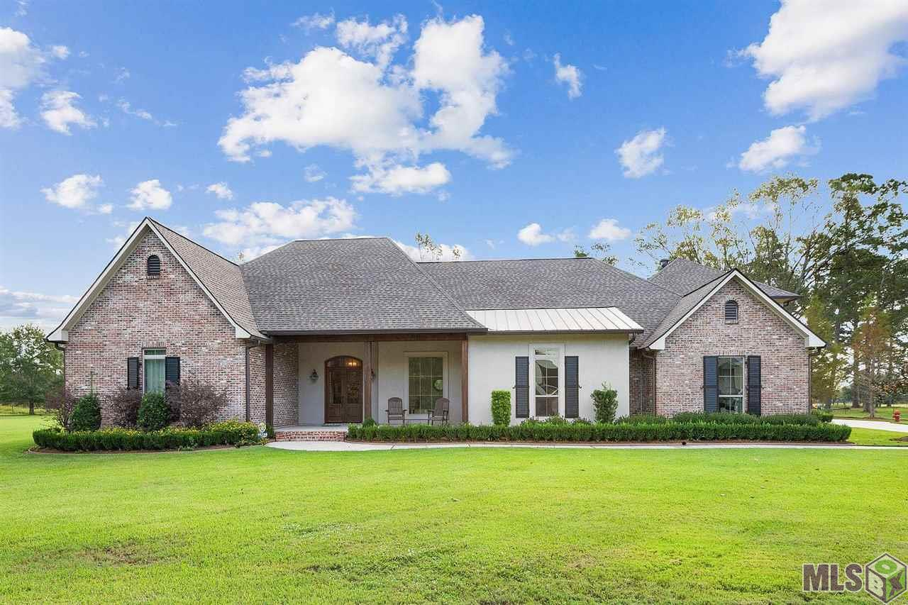 Beautiful custom home in Gonzales - Country living with all the conveniences of the city. This 4BR 4/2B house is on 1 acre with a manicured lawn, landscaping, lots of driveway for parking, and a gunite pool. Enter the foyer, office, living, formal dining area and kitchen and see the beautiful reclaimed oak floors. Triple split floor plan for plenty of privacy. Kitchen features a gas DCS range, stainless Viking refrigerator, huge island with lots of additional storage in addition to the custom cabinets and large walk in pantry. The counters in the kitchen are 3cm granite and there are plenty of windows for natural light. The home is equipped with primary suite that features a private bath, large walk in shower, soaking tub huge closet, his & her vanities and water closet. There are three additional bedrooms each with en-suite bathrooms. Laundry room with sink and mud area. Bonus room used for workouts/movies above 3 car garage. Views of the pool area and back yard are available from the primary suite, living area and enclosed patio area. Enclosed patio equipped with ice maker, mini fridge, and split AC unit. This home also features post tension slab, whole home generator and solar panels to reduce electricity costs. This is a must see home, schedule your appointment today!!!